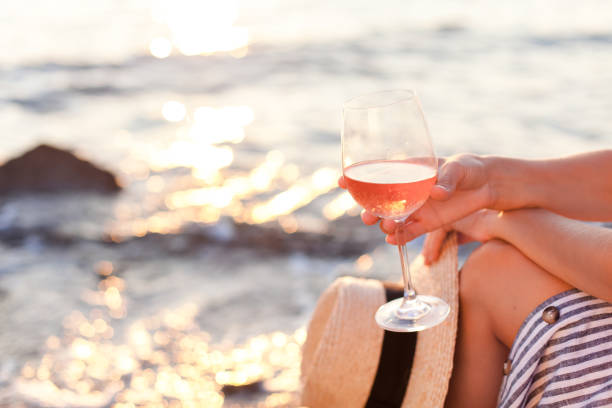 Girl is sitting on sea beach with wineglass of wine at sunset in summer vacation in resort. Tourist woman in striped dress with straw hat is enjoying life, relaxing, drinking, traveling. stock photo