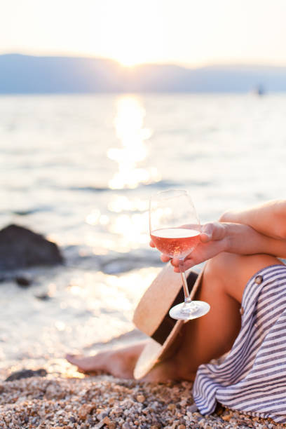Girl is sitting on sea beach with wineglass of wine at sunset in summer vacation in resort. Tourist woman in striped dress with straw hat is enjoying life, view, relaxing, drinking, traveling. stock photo
