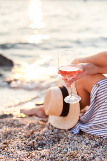 Girl is sitting on sea beach with wineglass of wine at sunset in summer vacation in resort. Tourist woman in striped dress with straw hat is enjoying life, view, traveling, relaxing, drinking. stock photo