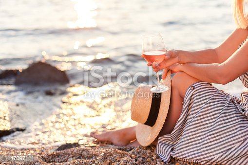 Girl is sitting on sea beach with wineglass of wine at sunset in summer vacation in resort. Tourist woman in striped dress with straw hat is relaxing, drinking, traveling and enjoying life.