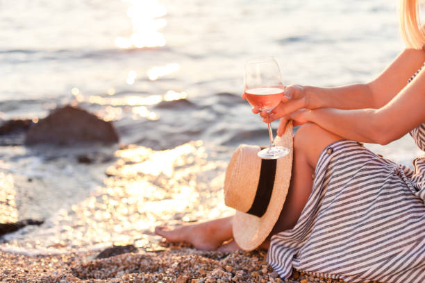 Girl is sitting on sea beach with wineglass of wine at sunset in summer vacation in resort. Tourist woman in striped dress with straw hat is relaxing, drinking, traveling and enjoying life. stock photo