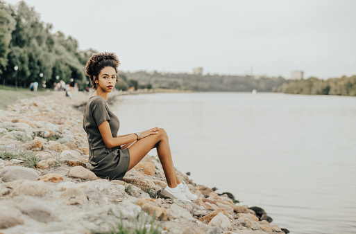 A girl is sitting on stones of the embankment
