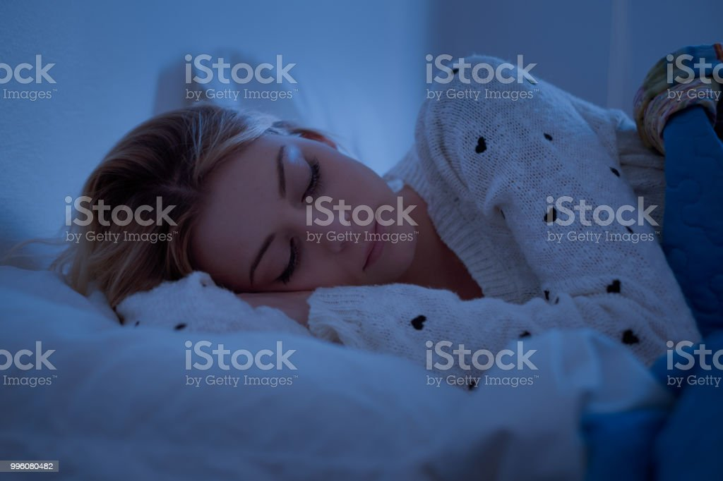 Girl is sleeping with her face on the pillow stock photo