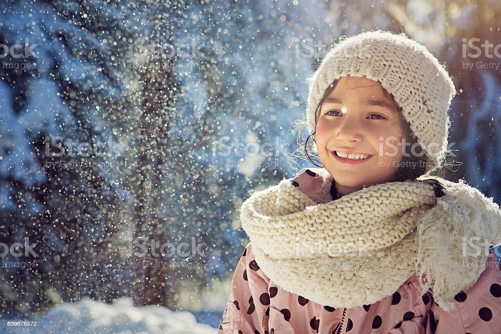 Girl is standing under the falling snow stock photo