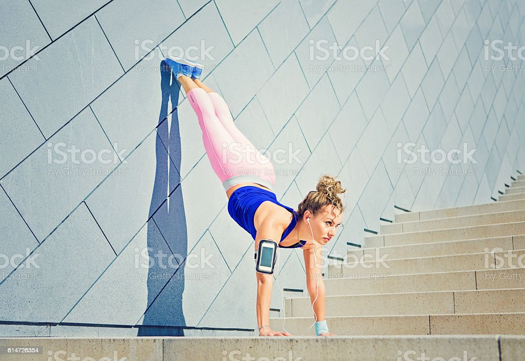 Girl is stretching on the city stairs stock photo