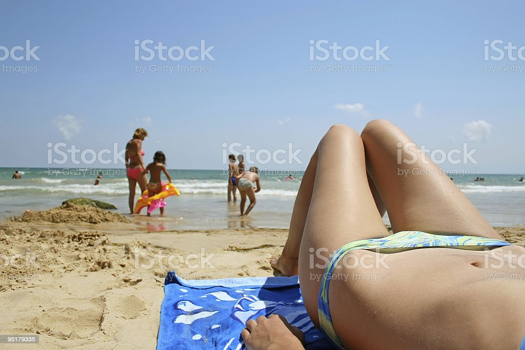 Girl is sunbathing on the beach stock photo