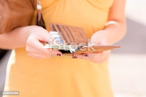 istock Girl is taking out money from wallet 538896088