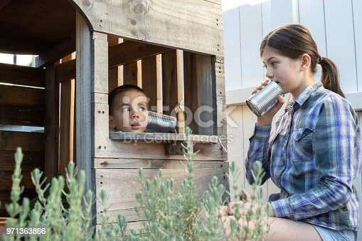 A 3-year old eurasian boy is inside a wooden playhouse and communicating with his 11-year old sister using an old fashioned string telephone