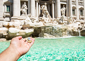 istock Girl is throwing coin at Trevi Fountain 1165387325