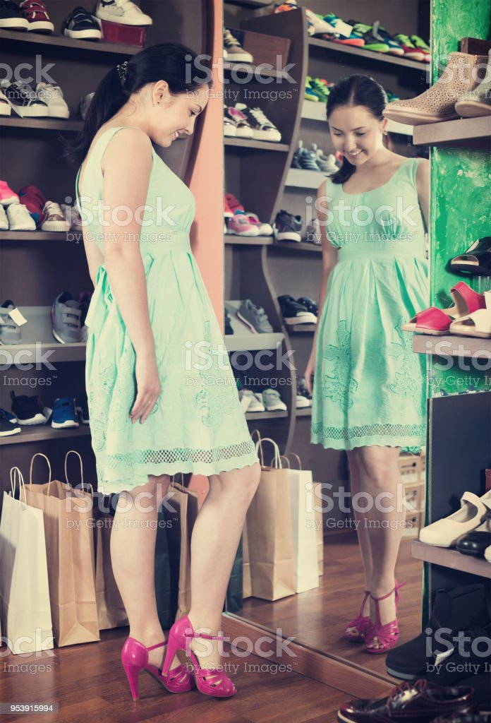 Girl is trying on heeled sandals  in shoes shop stock photo