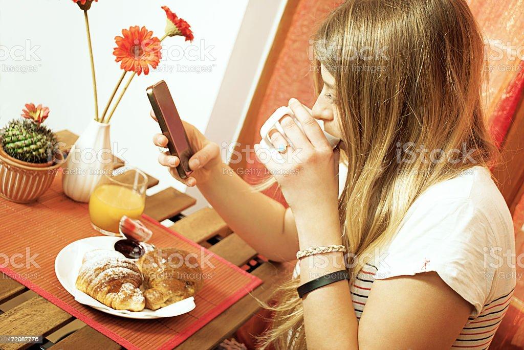 Mädchen ist mit smartphone während das Frühstück – Foto