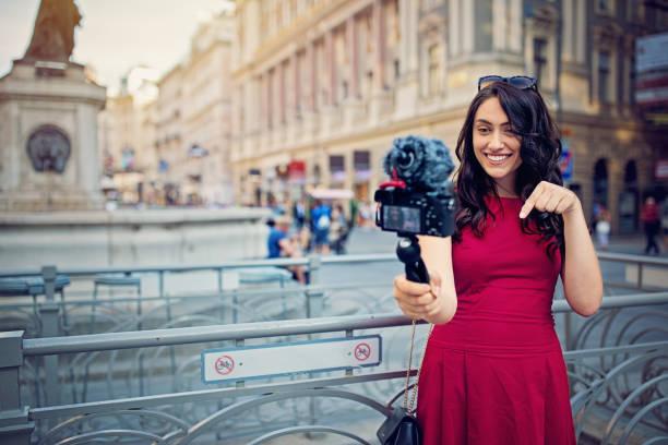 mädchen ist vlogs in der fußgängerzone des stadtzentrums - reiseblogger stock-fotos und bilder