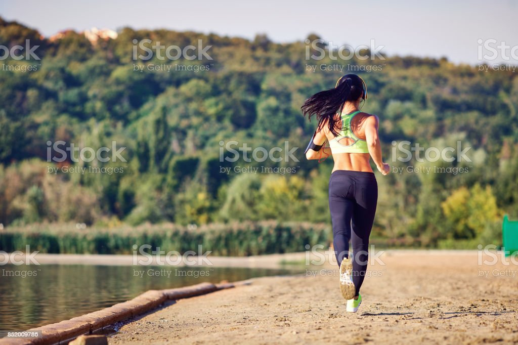 A girl jogging in the park. stock photo