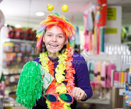 Portrait of happy comically dressed girl joking in festive accessories shop