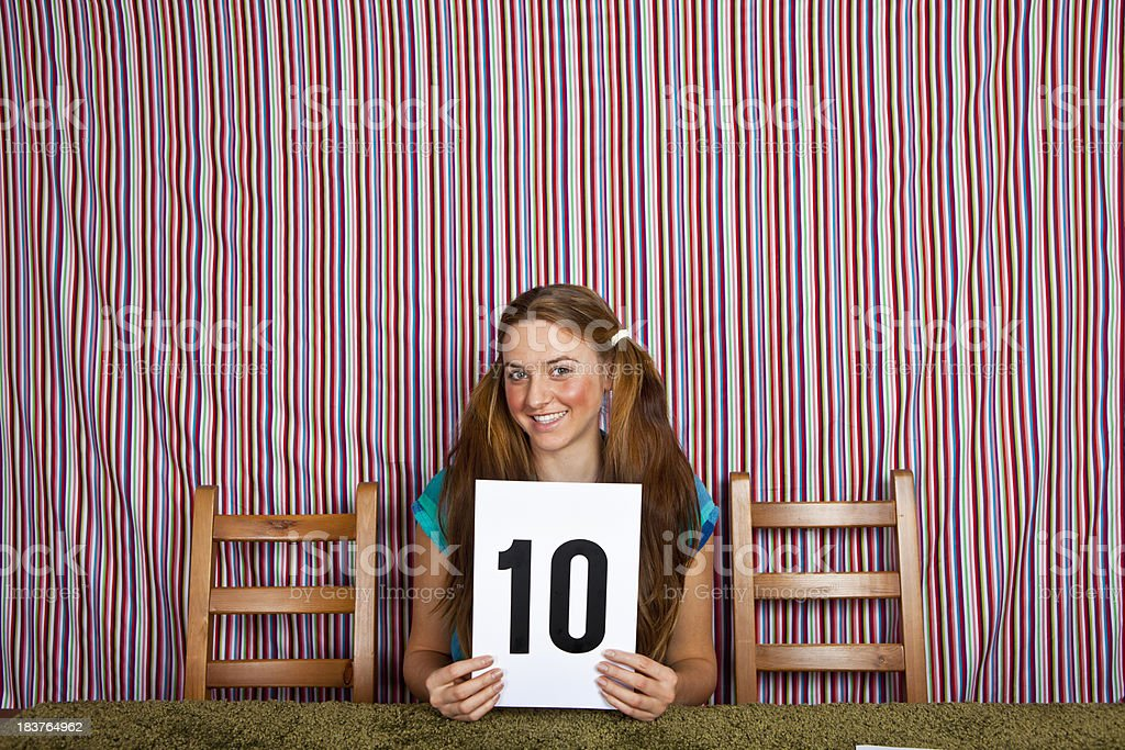 Girl judge holding up the perfect score royalty-free stock photo