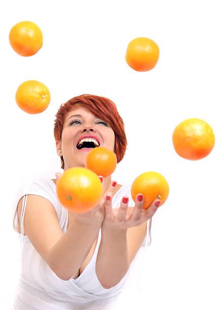 Girl juggling orange stock photo