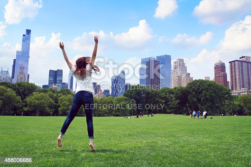 New York, United States - June 19, 2015: Girl jump in the Central Park with Manhattan buildings panorama in the New York City.