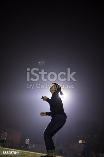 istock girl jump into the sky with floodlight behind 688287644