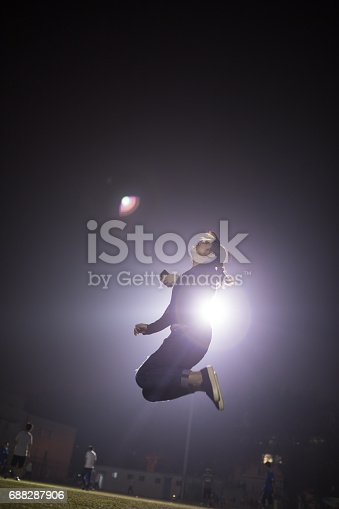 istock girl jump into the sky with floodlight behind 688287906