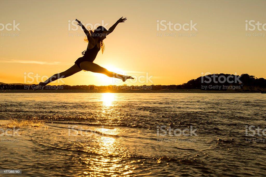 Girl jumping across water stock photo