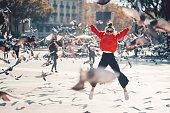 Young girl at Placa de Catalunya jumping happily among the pigeons