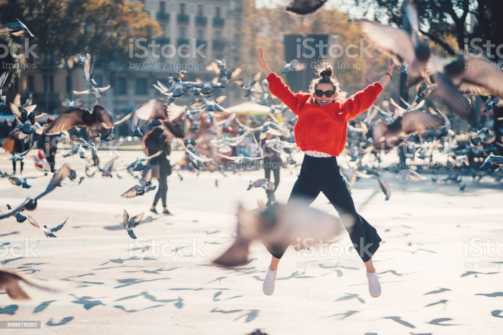 Girl jumping from joy in Barcelona stock photo