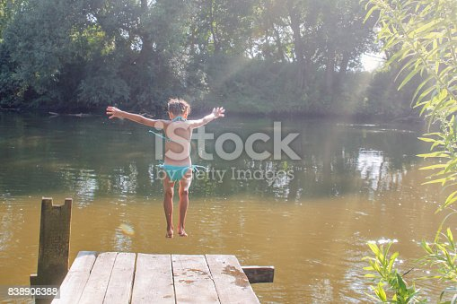 509813720 istock photo Girl jumping from the bridge into the water.Swimming in the river in summer. 838906388