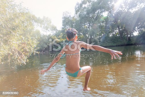 istock Girl jumping from the bridge into the water.Swimming in the river in summer. 838909360