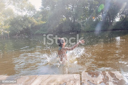 istock Girl jumping from the bridge into the water.Swimming in the river in summer. 838909804