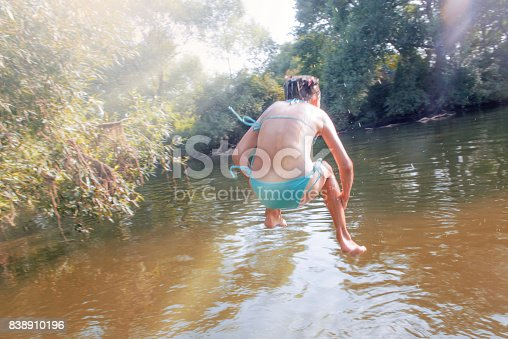 509813720 istock photo Girl jumping from the bridge into the water.Swimming in the river in summer. 838910196