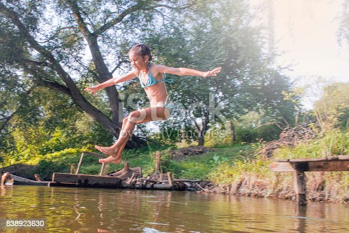 509813720 istock photo Girl jumping from the bridge into the water.Swimming in the river in summer. 838923630