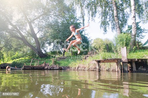 509813720 istock photo Girl jumping from the bridge into the water.Swimming in the river in summer. 839007682