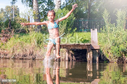 istock Girl jumping from the bridge into the water.Swimming in the river in summer. 839790798