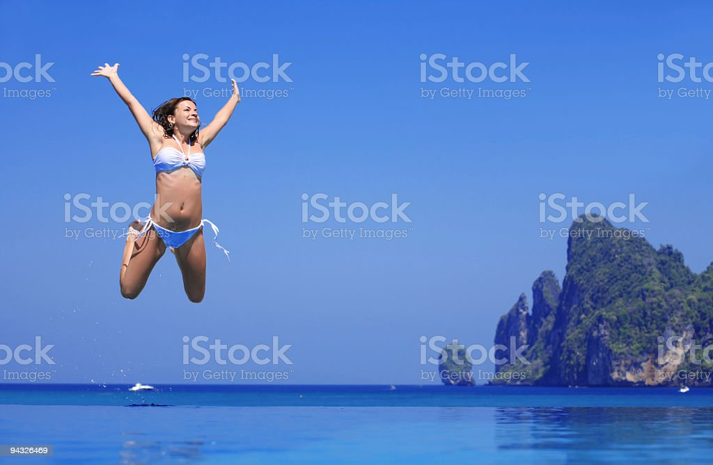 Girl jumping in blue water. royalty-free stock photo