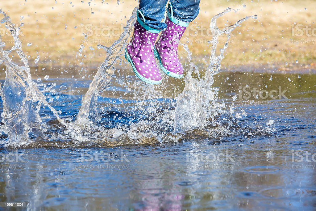 Girl Jumping In Large Water Puddle in Early Spring stock photo