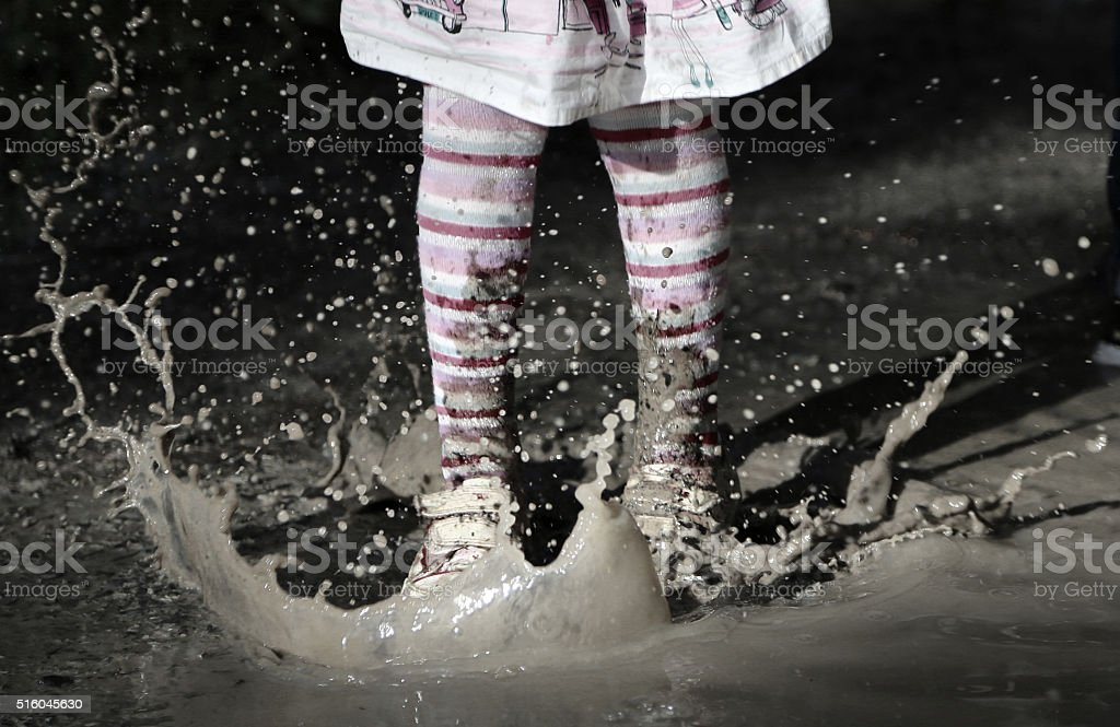 Girl jumping in muddy puddles stock photo