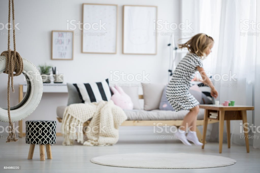 Girl jumping in room stock photo