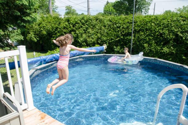 Mädchen im Pool springen, während ihr Bruder entspannend auf einer aufblasbaren Pool-Matratze während Tag des Sommers – Foto