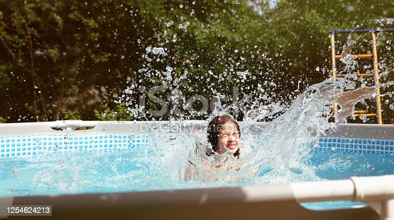 Laughing young girl with jumping into backyard swimming pool and making big splash.