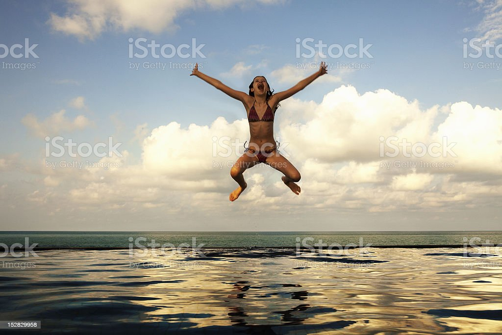 Girl jumping into infinity pool stock photo