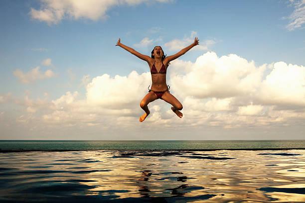 Girl jumping into infinity pool stock photo