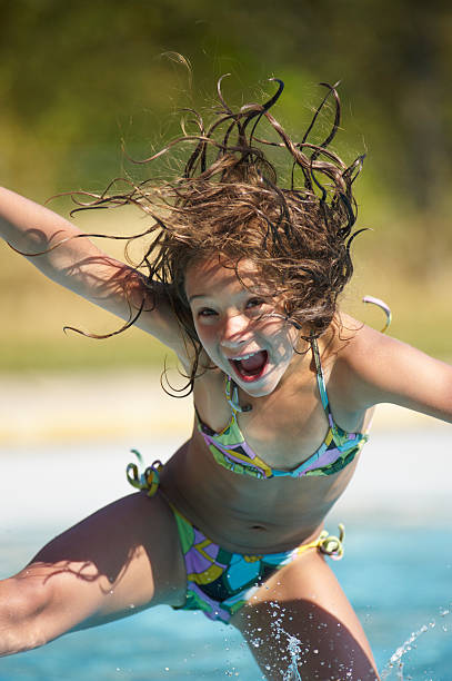 girl jumping into swimming pool - girl alone in swimsuit stock photos and pictures