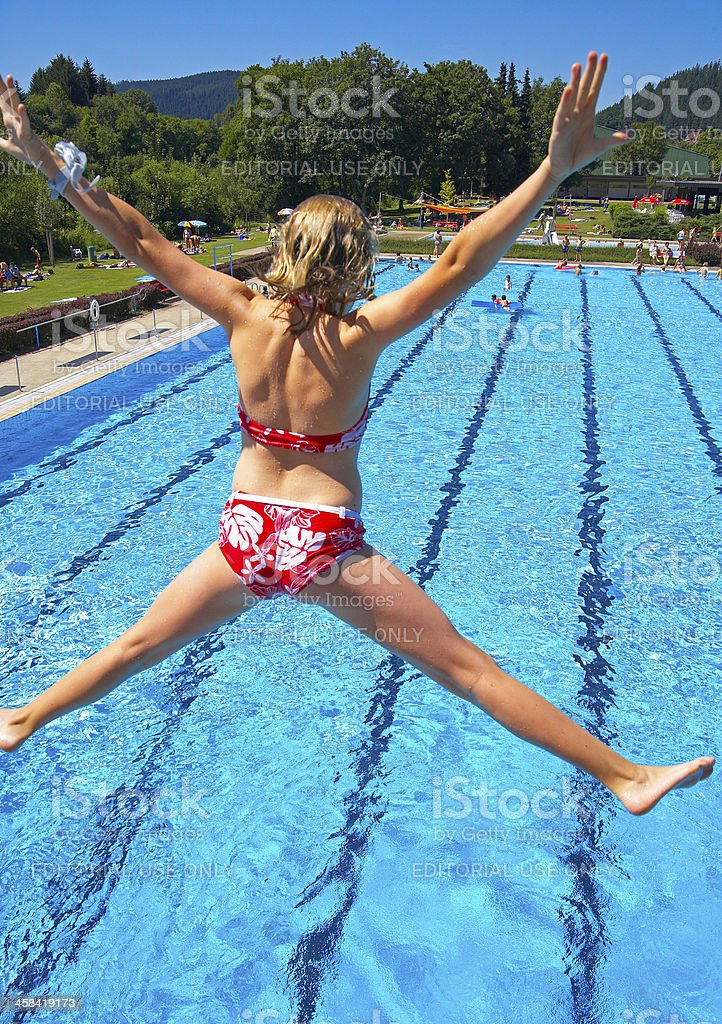 Girl jumping into water stock photo