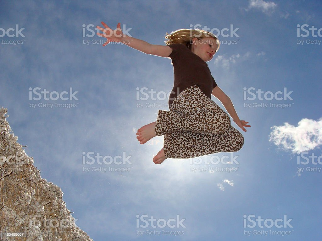 Girl Jumping off Cotten Seed stock photo
