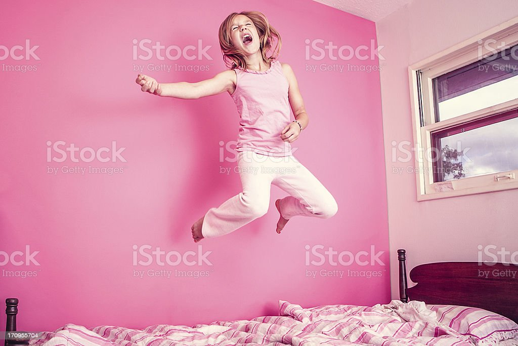 Girl Jumping on Bed in Pink Room stock photo