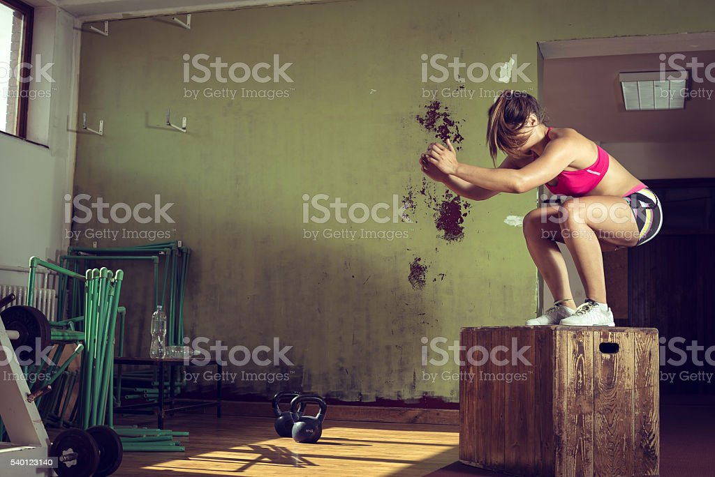 Girl jumping on box in gym stock photo
