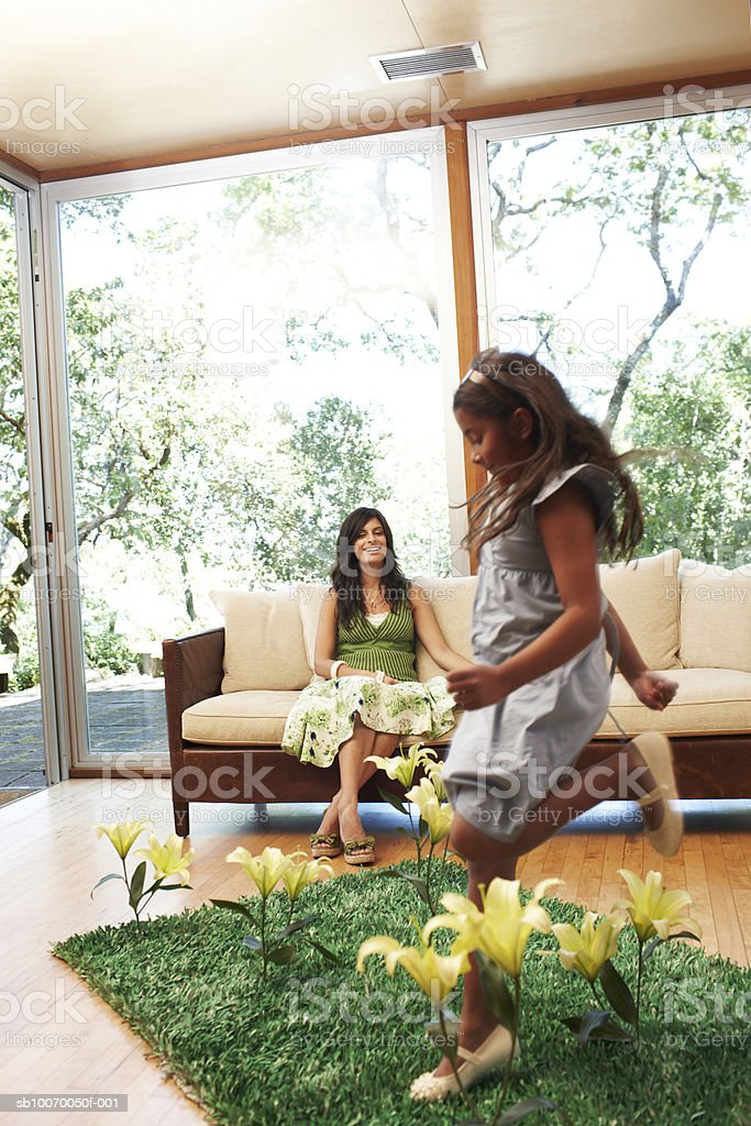 Girl (6-7 Years) jumping on grass patch with flower in living room, mother watching royalty free stockfoto