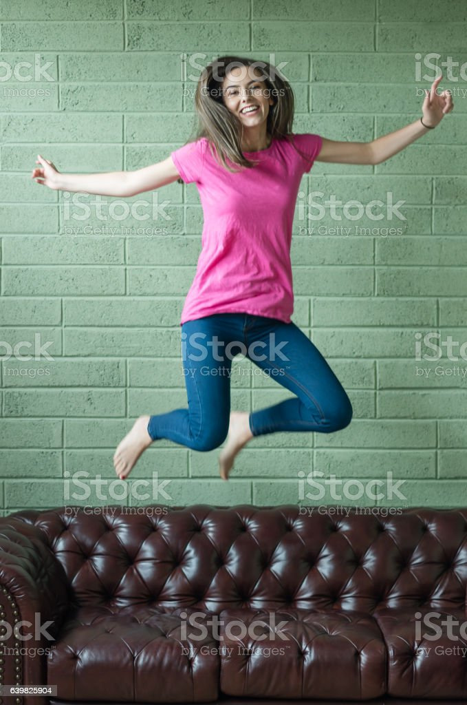 Girl jumping on sofa stock photo