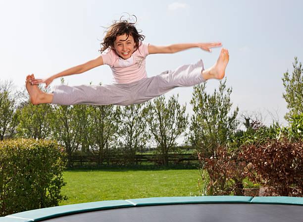 mädchen springen auf trampolin - gartentrampolin stock-fotos und bilder