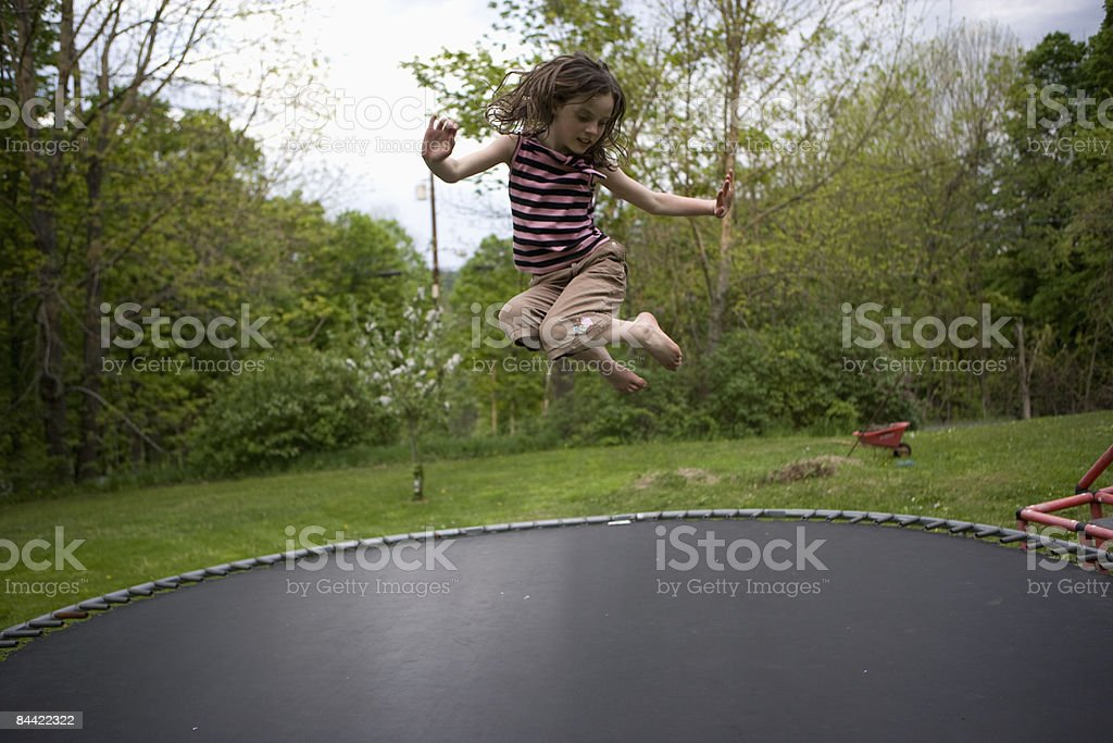 Girl jumping on trampoline royalty-free stock photo